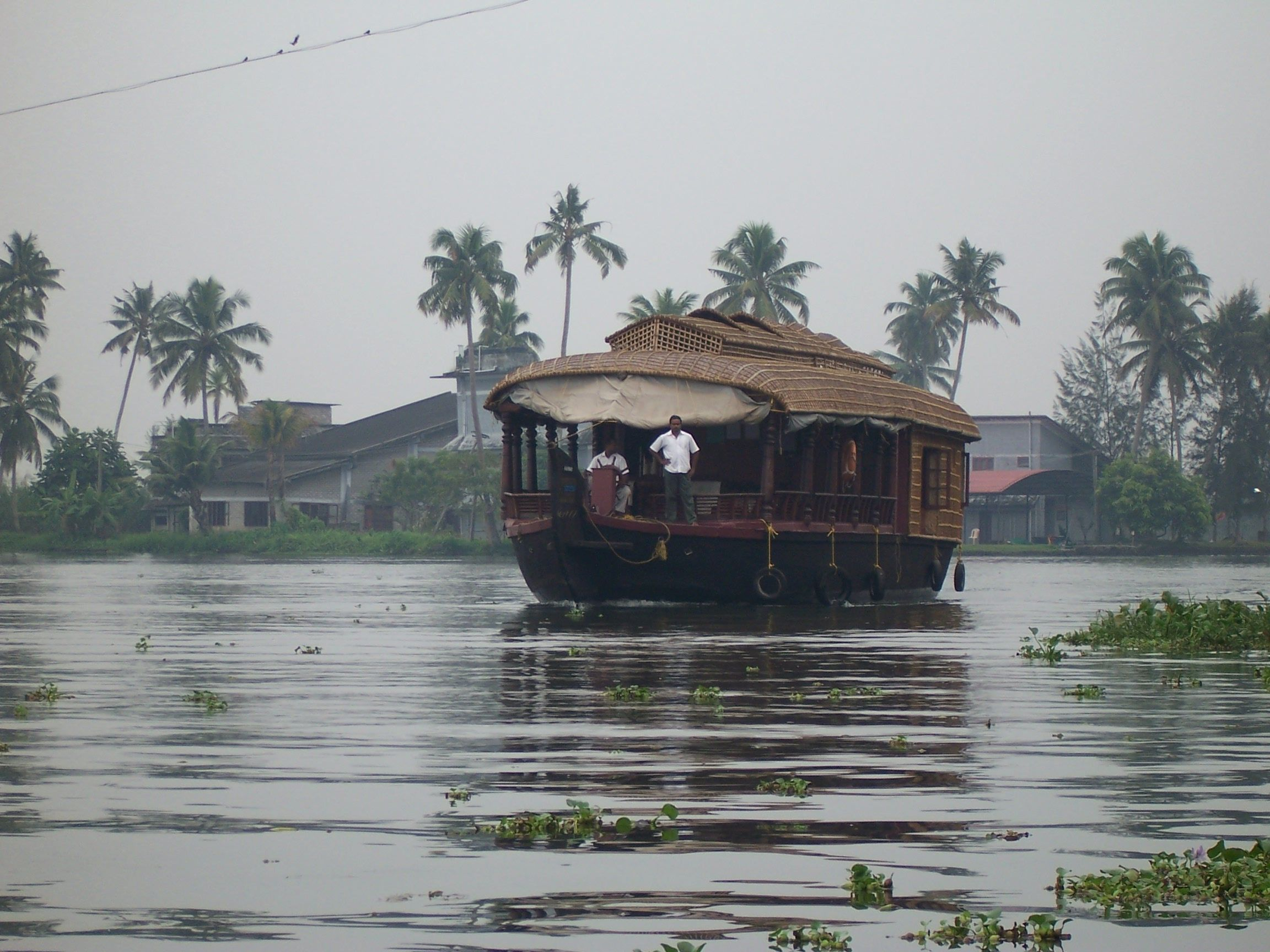 A house boat chugs through the morning haze on Lake Vembanad. The day after rains in the area.